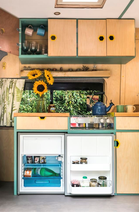 A spacious kitchen with large fridge in a campervan conversion