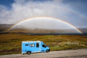 A blue campervan drives along a road next to a loch in Scotland with a rainbow in the background