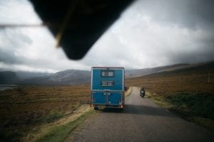 The view of the back of a blue campervan from a car with a surfboard on the roof  on an empty road in the highlands of Scotland