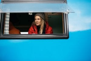 A lady in a red coat and winter hat looks out the window of a blue campervan