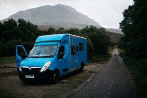 A blue selfbuilt campervan parked on the roadside with mountains in the background