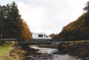 Campervan crossing a bridge over a stream in Skye, Scotland