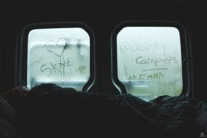 Windows of a campervan with condensaion where a love heart, Skye and @quirky campers Emma have been written out by fingers