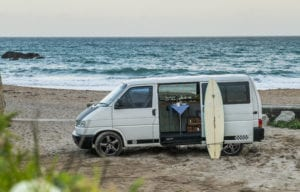A campervan with surf board on the beach with the sea in the background