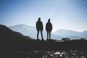 A couple's silhouette looking over mountains