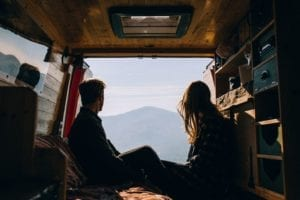 A couple sat in the back of their selfmade quirky campervan on their honeymoon