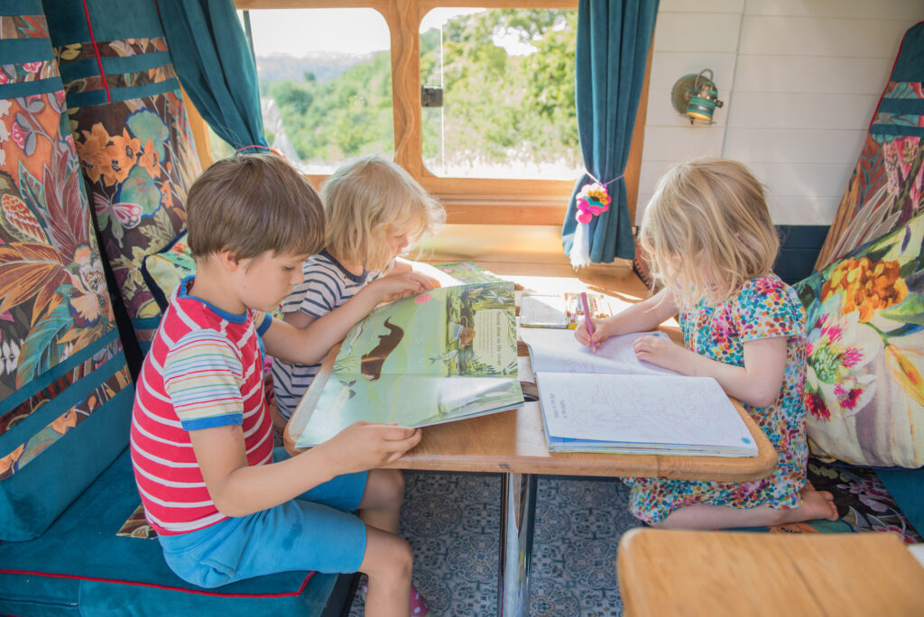Children entertained in a campervan reading books and listening to audiobooks