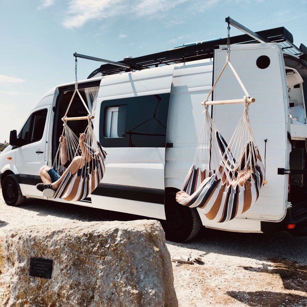 Swinging from hammocks in front of a campervan